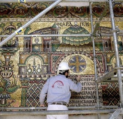 PHOTO BY AP/NASSER NASSER A restoration expert works on a mosaic inside the Church of the Nativity in Bethlehem. The church, originally built in the fourth century and rebuilt in the sixth, is thought to have been built on the site where Jesus was born.